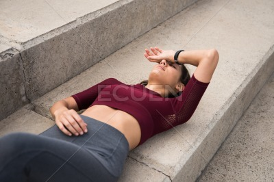 Sporty young brunette lying on stairs