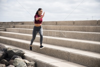 Young pretty brunette doing fitness on stairs