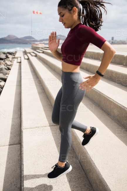 Attractive fit female running down stairs stock photo