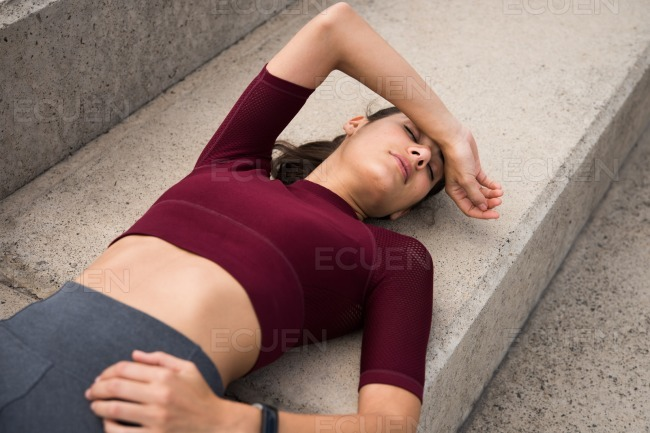 Sporty young brunette resting on stairs stock photo
