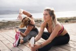 Two fit young women exercising in the sunlight