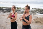 Two girls in fitness clothes with hands to hearts