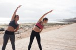 Two young women doing stretches outside