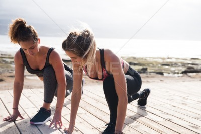 Beautiful young women exercising together outside