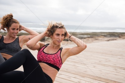 Fit young women doing knee raises outside