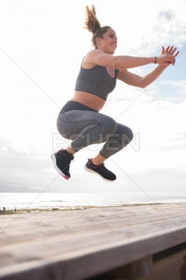 Pretty young woman jumping on stairs