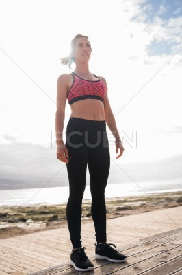 Pretty young woman standing in fitness clothing