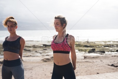 Sexy young women exercising by the sea