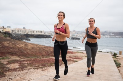 Smiling young women running by the seaside