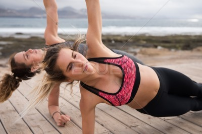 Two attractive young women exercising together
