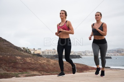Two pretty girls running in fitness clothes