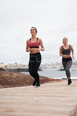 Young attractive females running on the boardwalk