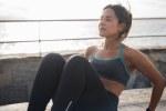 A young woman doing abdominal training outside