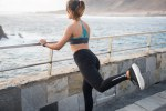 Girl in fitness clothing holding onto a railing
