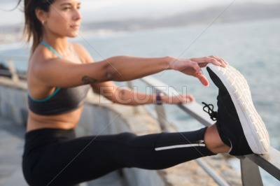 A fit young woman doing leg stretches