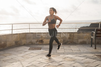 A pretty brunette running on the promenade
