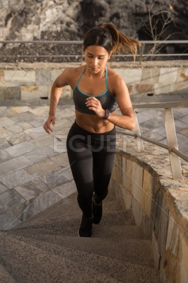 A sporty young woman focused on running