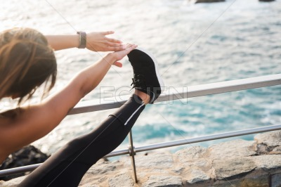 A woman doing stretches by the sea side