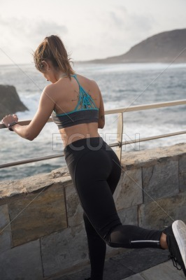 A woman in active wear standing by the ocean
