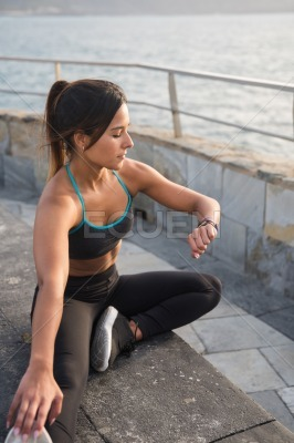 A woman in fitness clothes looking at her watch