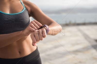 A woman in fitness clothing touching her watch