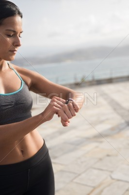 A young woman checks her watch outside