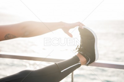 Leg up on a railing with hand touching feet