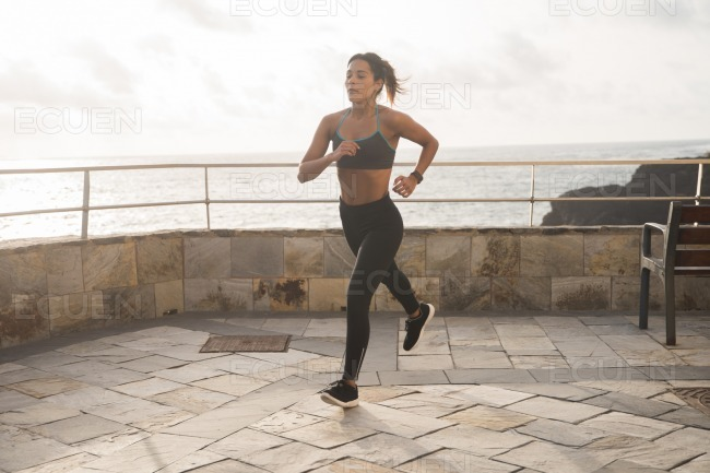 A pretty brunette running on the promenade stock photo