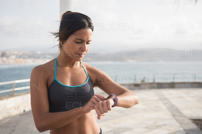 A young sporty woman looking at her smartwatch stock photo