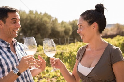 A man and woman drinking wine in a vineyard