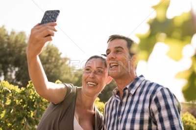 A man and woman taking a selfie in the vineyards