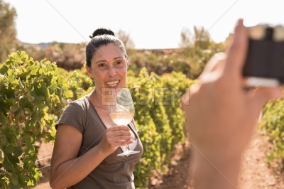 A man takes a photo of a woman in the vineyards