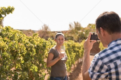 A man takes a photo of a woman in the winelands