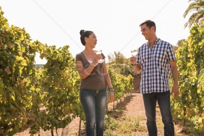 A woman and a man drinking wine in the vineyard