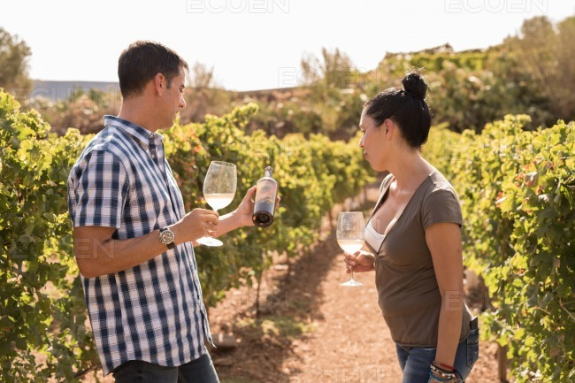 A man and woman looking at a bottle of wine