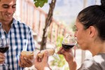 Couple eating bread and drinking wine at a vineyar
