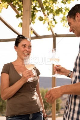 Couple chatting in a vineyard and drinking wine