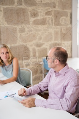Man and woman sitting at a desk talking
