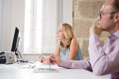 Man and woman sitting at a desk with pens in their