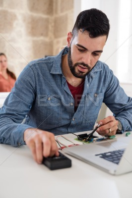 Man sitting at a desk working on electronics