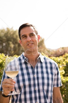 Man smiling and holding a glass of wine