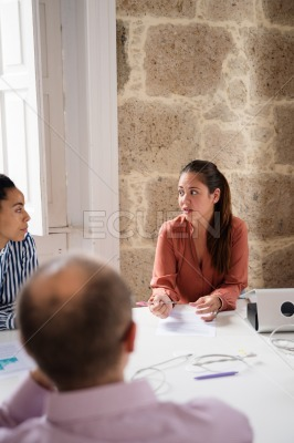 Three people at a desk in an office talking