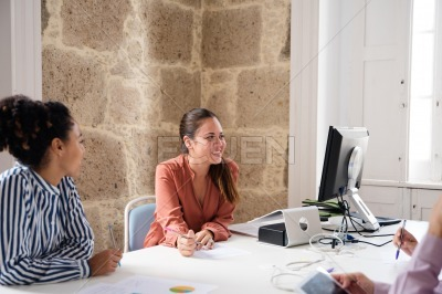 Three people sitting at a desk in an office