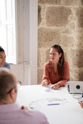 Three people sitting at a desk talking