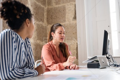 Two women sitting at a desk and one is talking