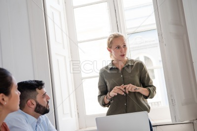 Woman standing in a room chairing a meeting