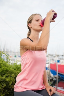 Young girl drinking from a purple plastic bottle