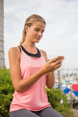 Young girl in gym outfit looking at her mobile