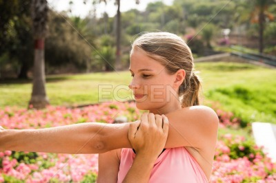 Young girl stretching her arm in the park