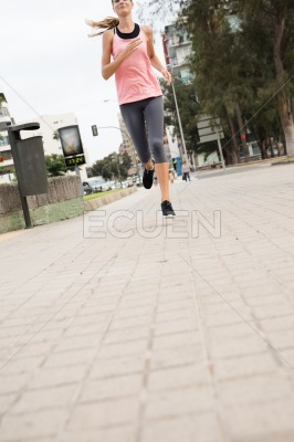 Young woman running past a trashcan